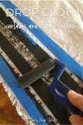 drop cloth with painters tape and paint roller applying black paint.