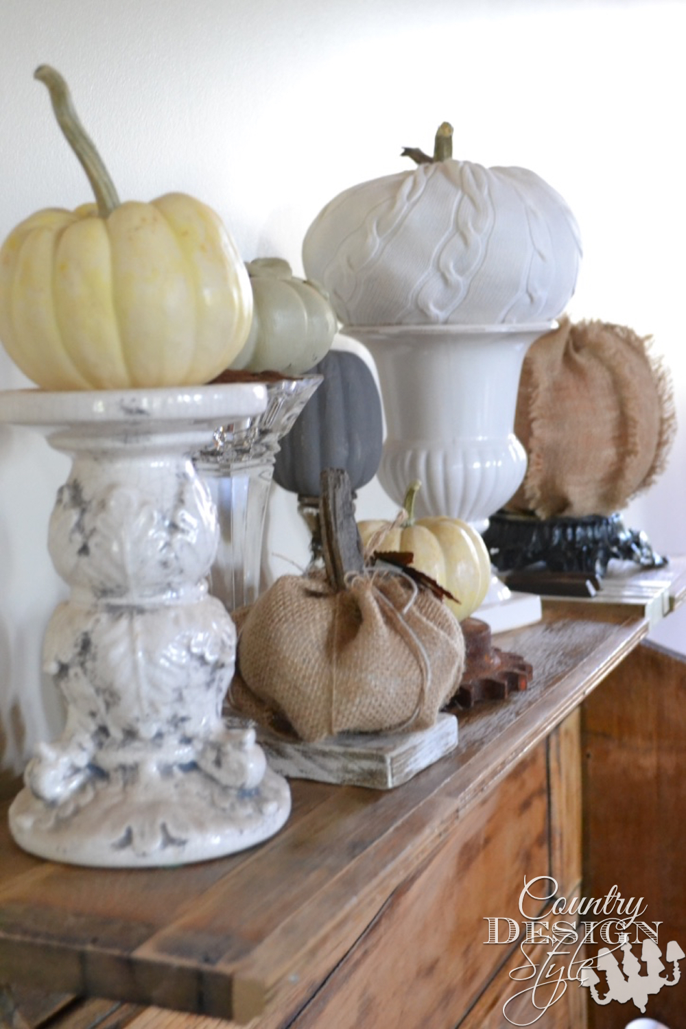 Give a pumpkin a lift. Place on candleholders vase or urn, rusty gear, chunk or wood or the base of a vintage lamp. | countrydesignstyle.com