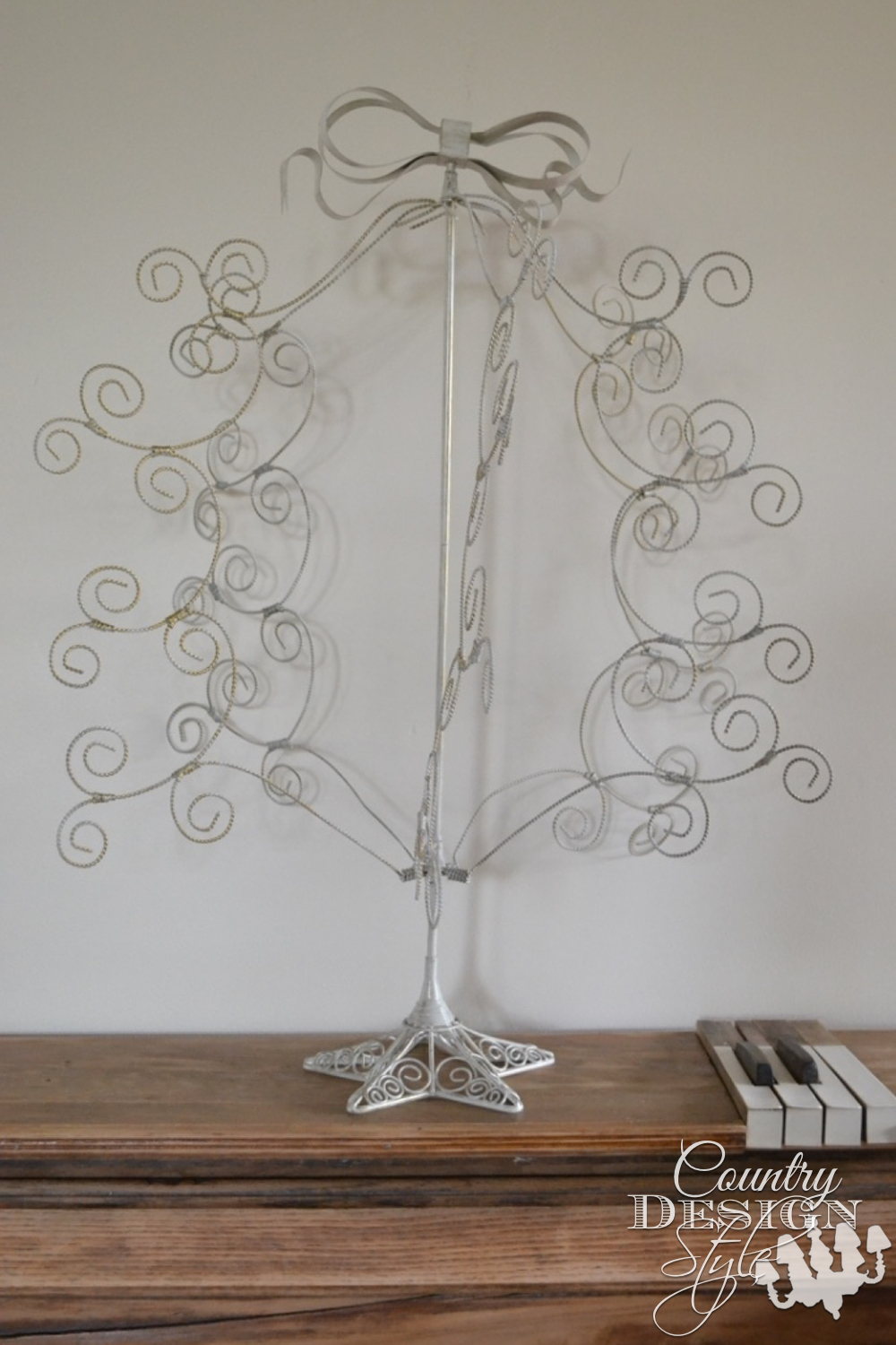 Wire ornament tree that holds ornaments or Christmas cards gets junked up the old spindles. Sitting on old organ turned mantel. | countrydesignstyle.com