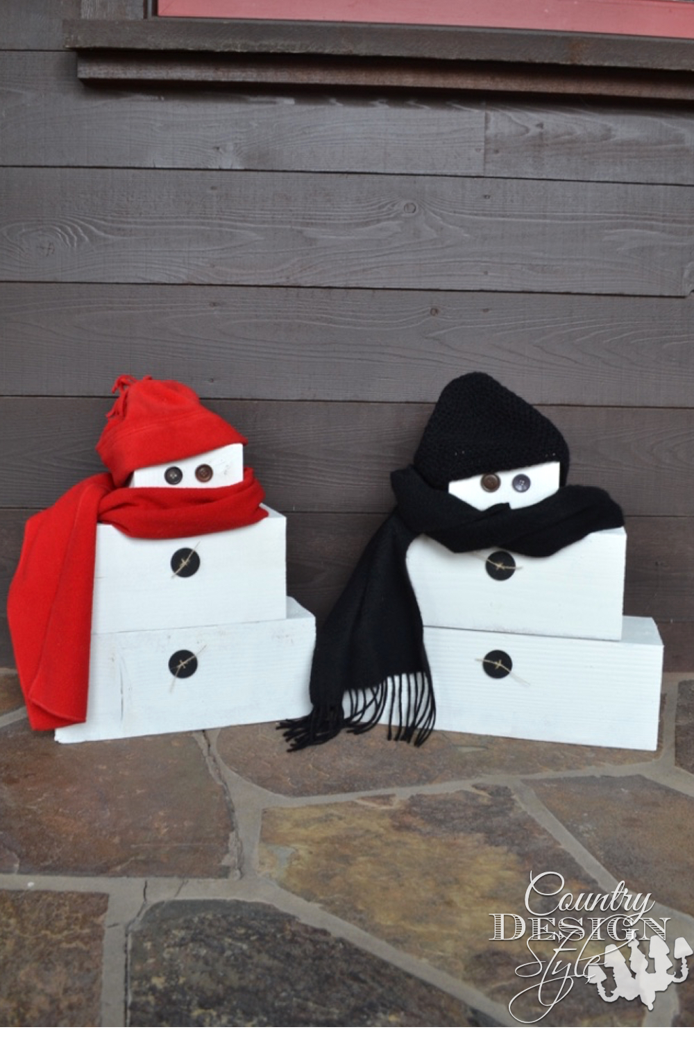Scrap pile wood from construction site is turned into a couple of snow people. Button eyes, scarves and knit caps. | countrydesignstyle.com