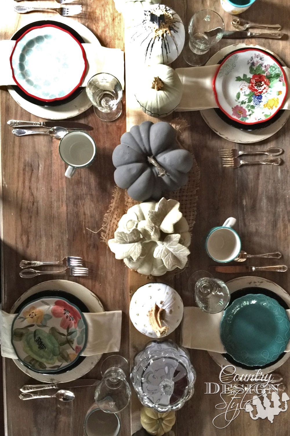 Thanksgiving table with natural colors on different type of pumpkins lined on a wood board runner. The place setting have loads of color with rustic chargers. | countrydesignstyle.com