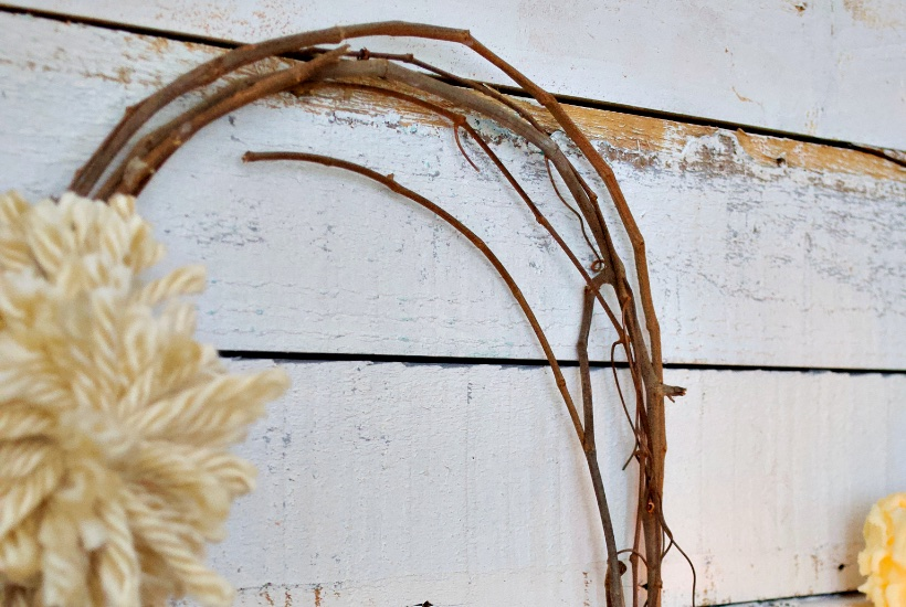 Winter grapevine wreath with pom pom on rustic white paint wood wall.