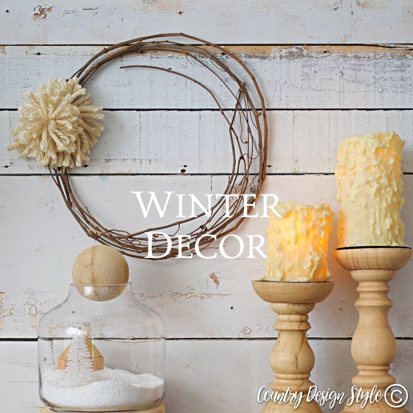 Grapevine wreath with pom pom, candles, and winter scene in a jar.