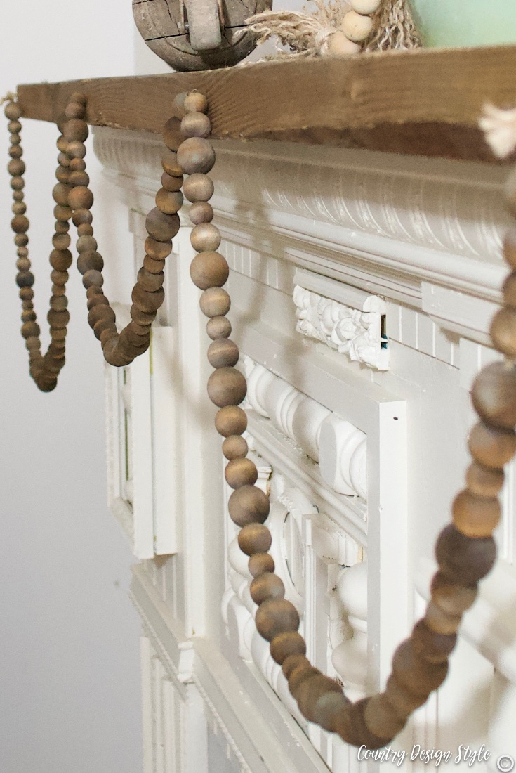 rustic wood garland hanging from rustic mantel