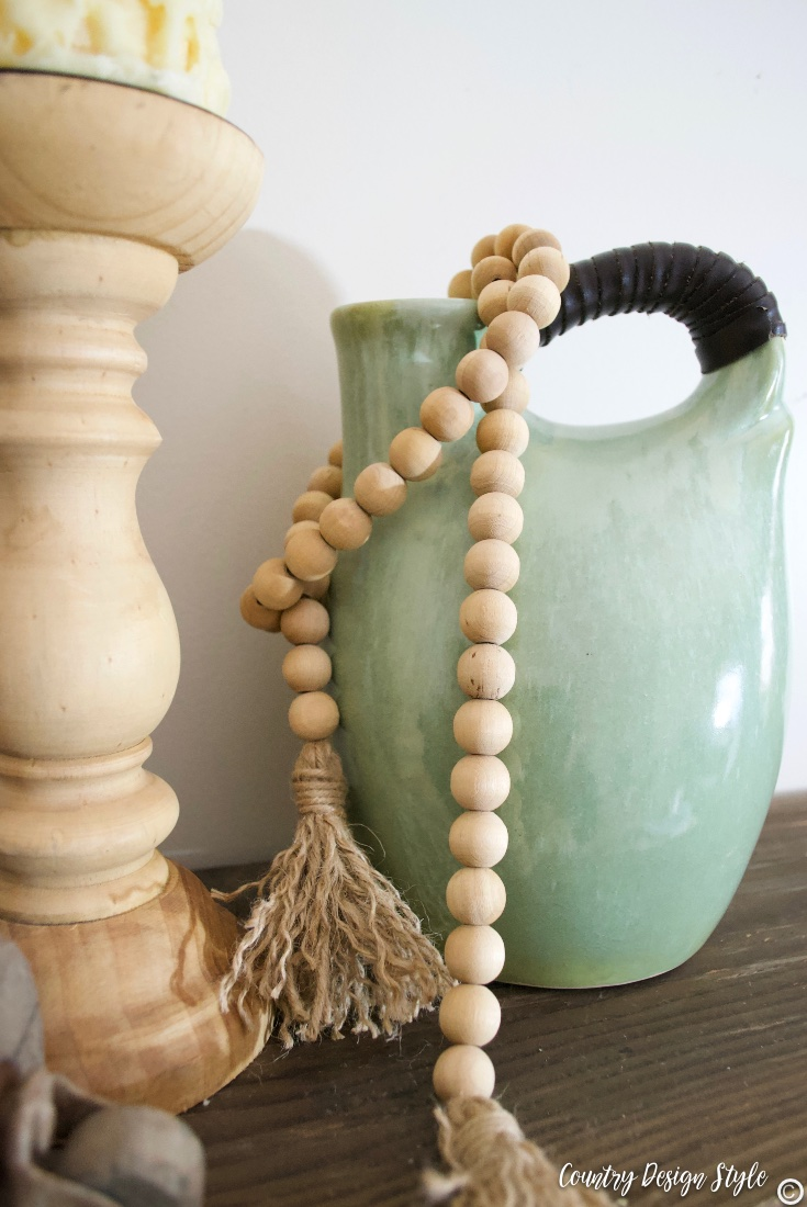 Green vase with wood beaded garland and wood candleholder