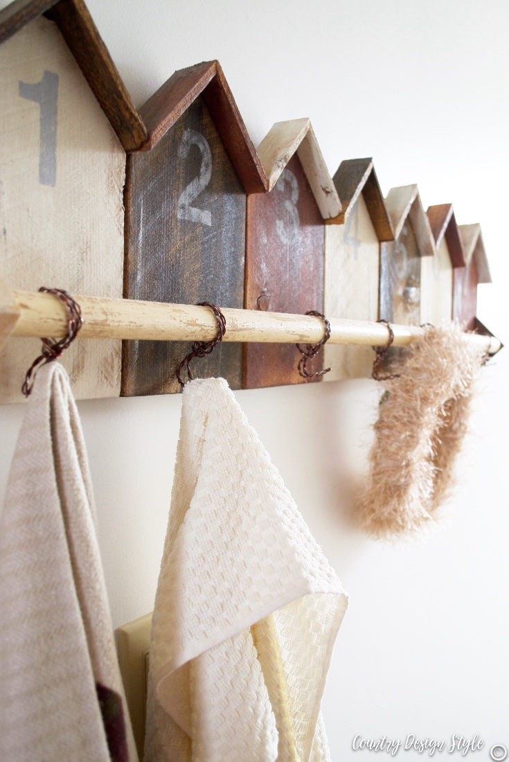 Wood house pieces painted or stain in cabin colors with hooks hanging from a dowel