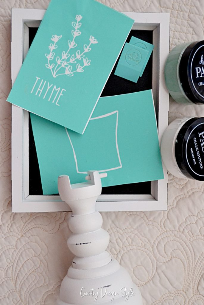 Spindle base that holds a 5 by 7 chalkboard sign with teal transfers, squeegees, and two pots of chalk paste.