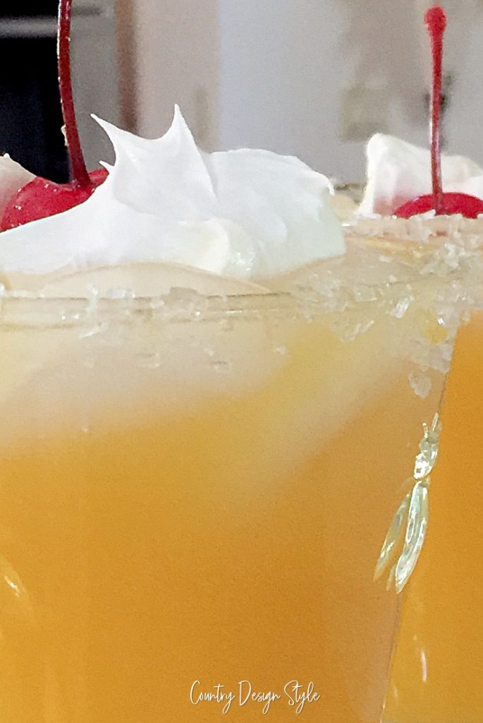 close up of orange juice with cherry vodka topped with whipped cream and cherries.