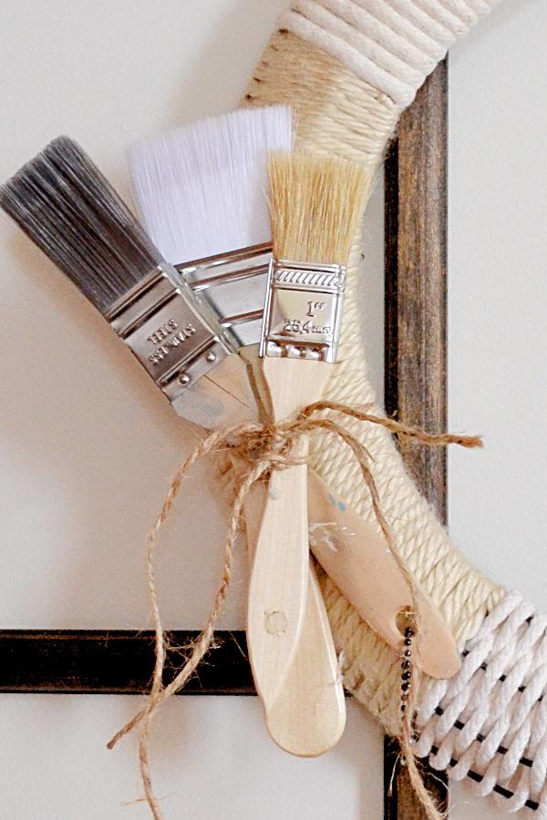 three paintbrushes tied on wreath