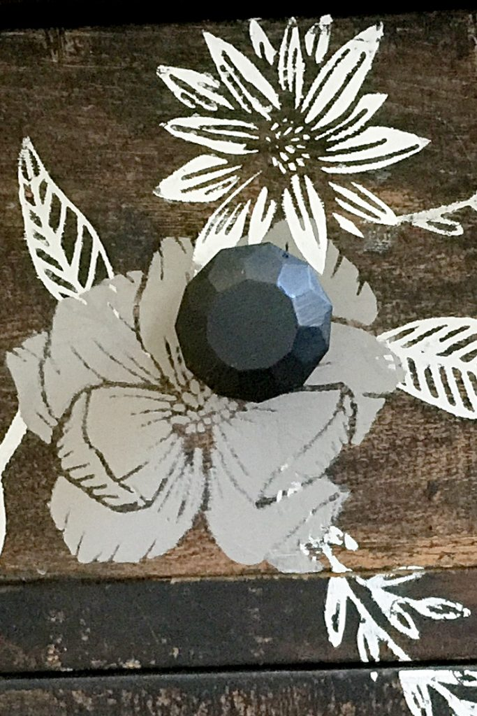 Close up of flowers and leaves on dresser.