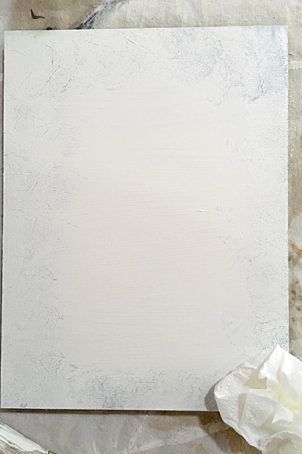 white painted board with some of the paint removed around the edges to reveal brown paint.