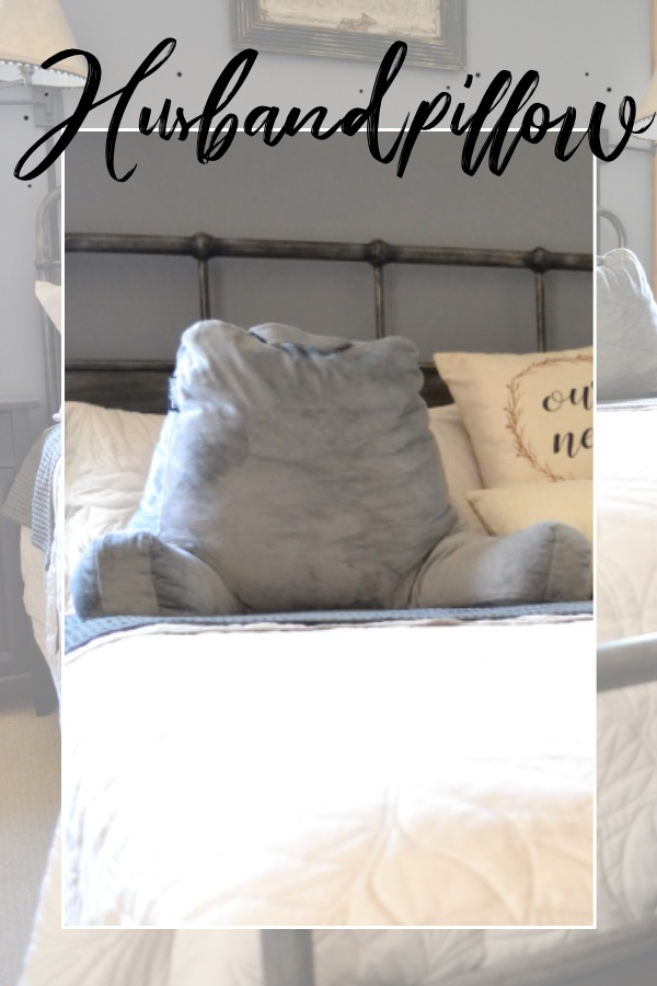 Iron bed with gray husband pillow and cream bedspread.