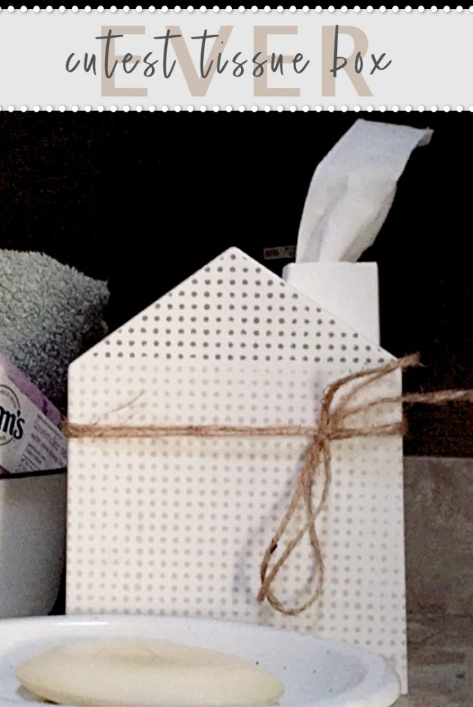 white tissue box in the shape of a house with a chimney to pull the tissues from .