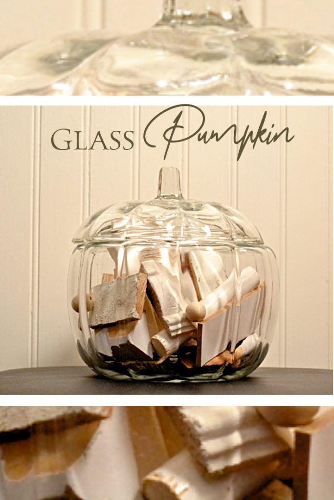 Glass pumpkin filled with white scrap wood pieces.