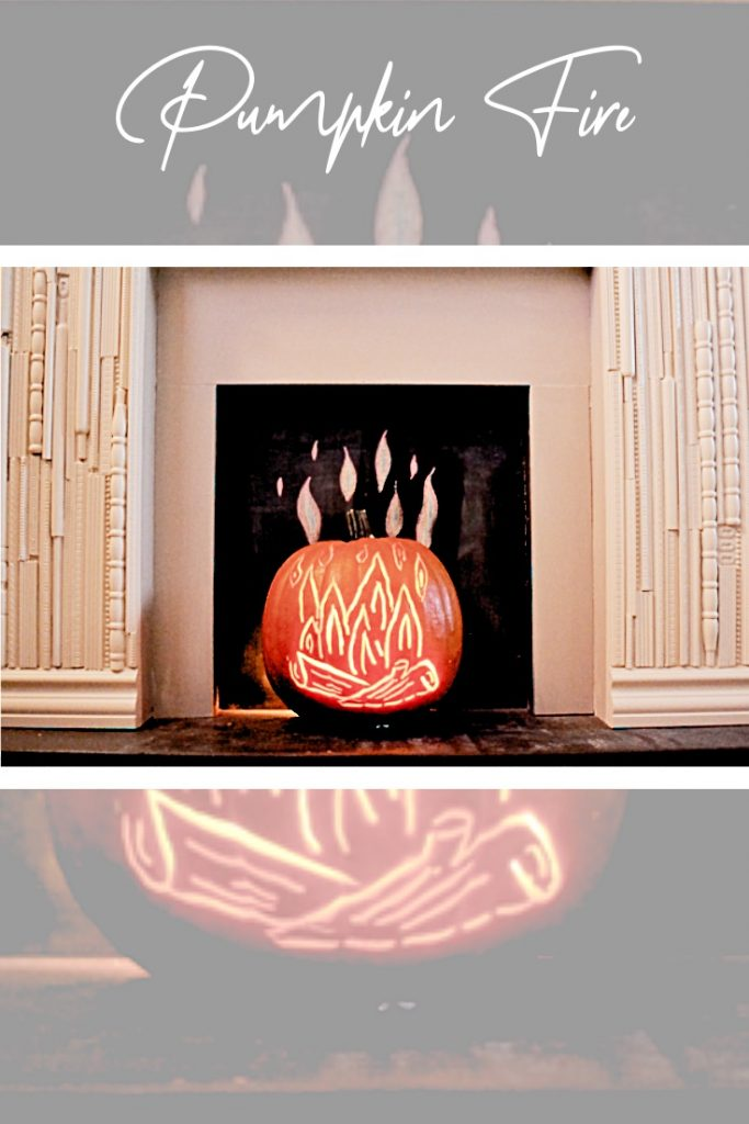 orange pumpkin with fire carved and sitting in fake fireplace.
