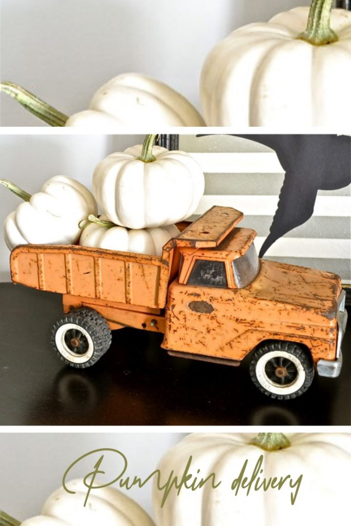 Orange metal toy truck filled with white pumpkins