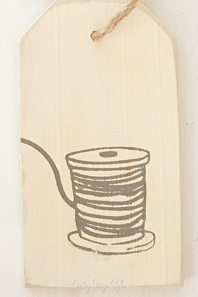 cream painted tag with image of thread spool