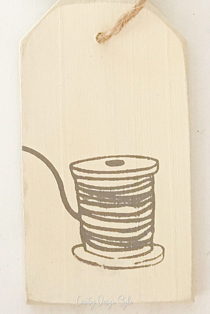 cream painted wood tag with image of thread on spool applied with transfer.
