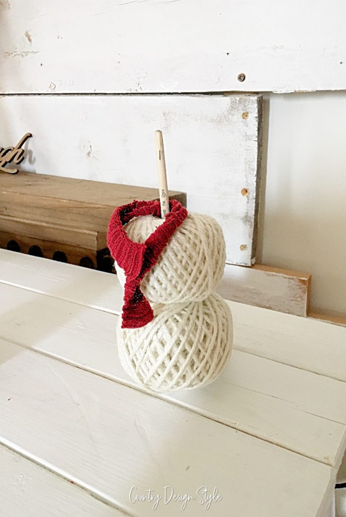 two yarn balls stacked on paintbrush with scarf wrapped around paintbrush