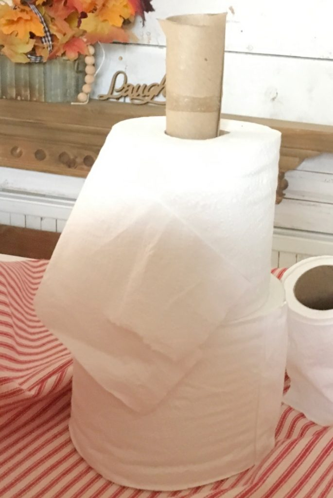Two toilet paper rolls with paper towel roll in the middle.