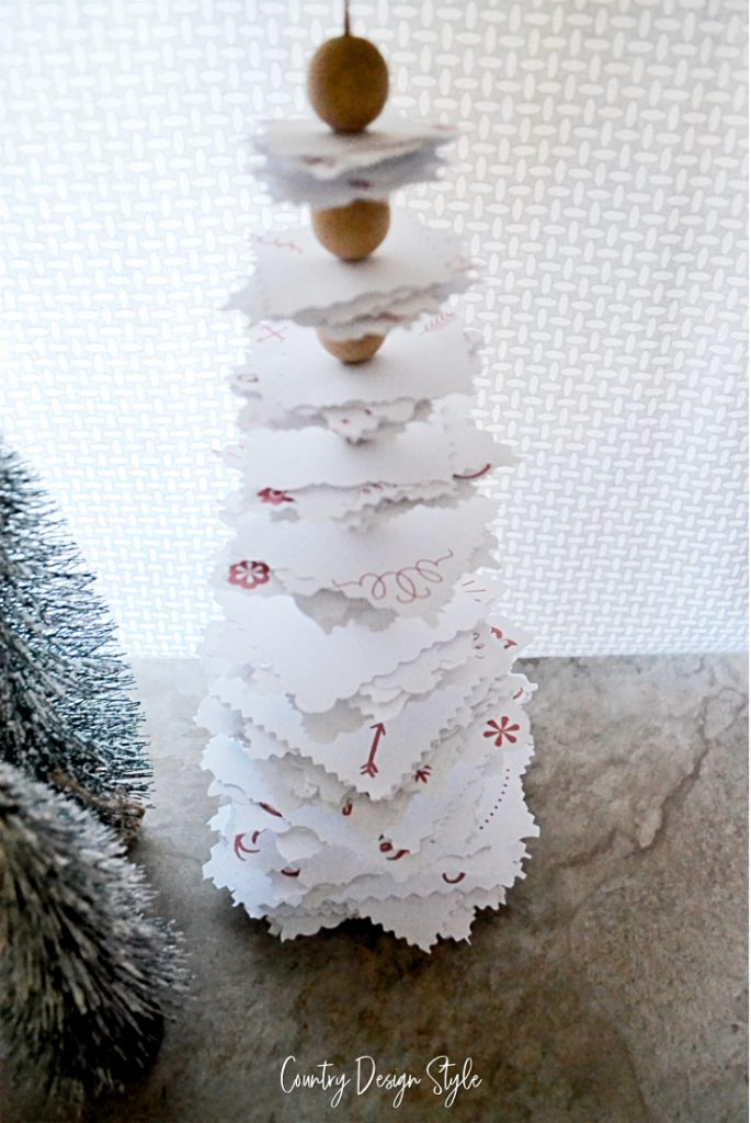 Paper tree with red elements and decorative cut edges.