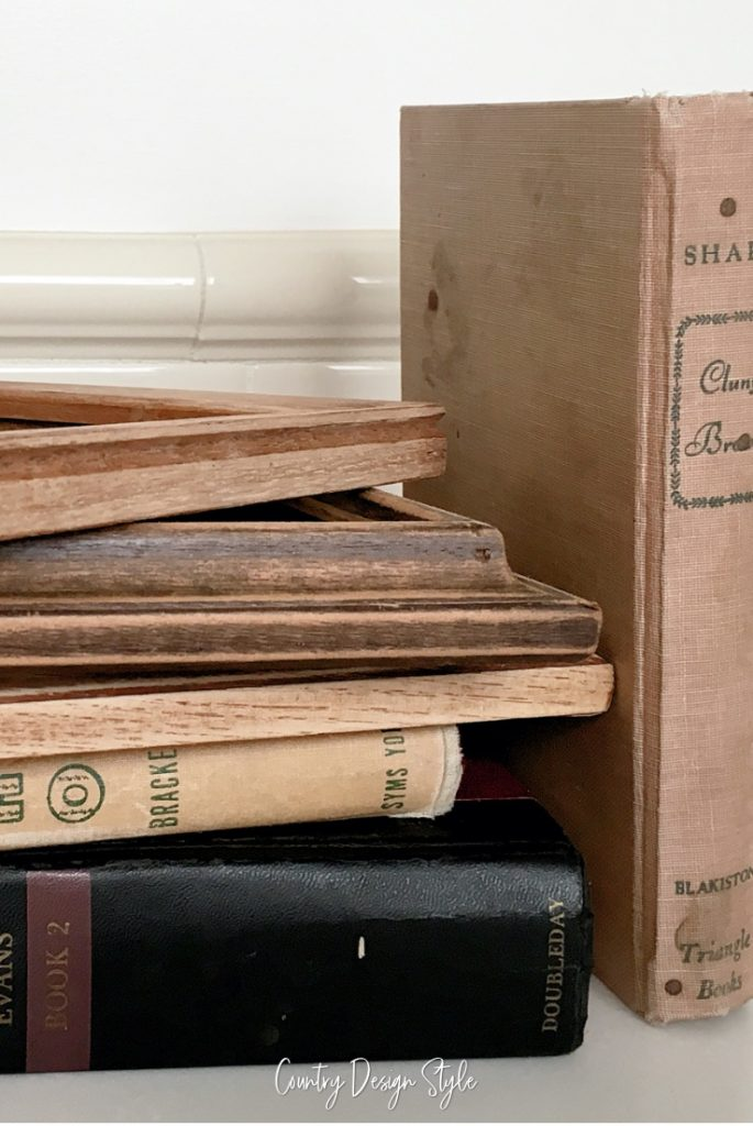 three old books and frames stacked