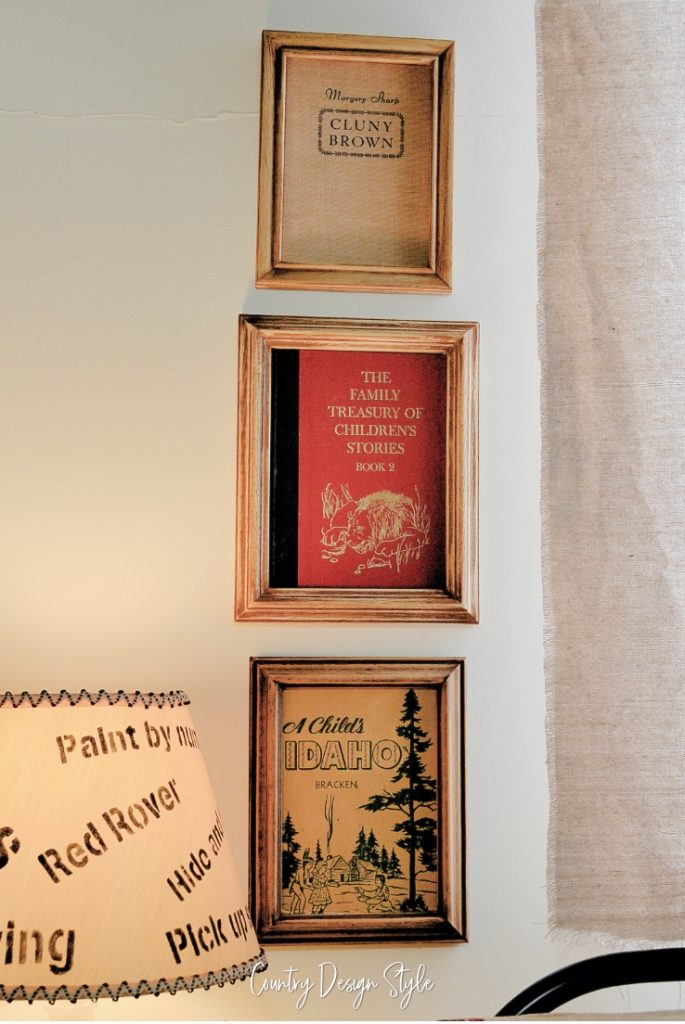 three books in frames hanging