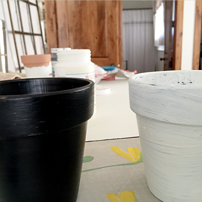 black painted pot and white painted pot