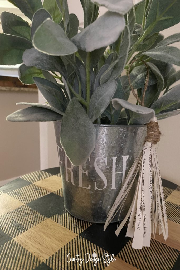 Tassel hanging from the metal pot with faux green plants